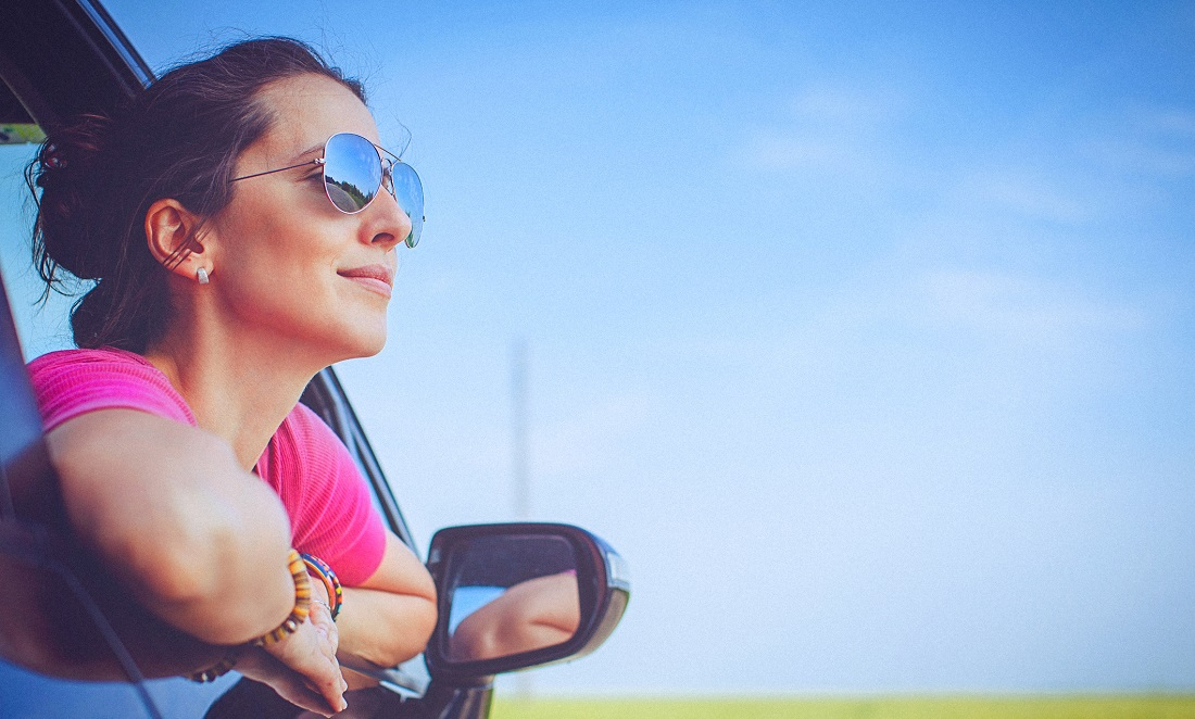 Woman in pink shirt and sunglasses, leaning out car window and smiling with blue sky in the background