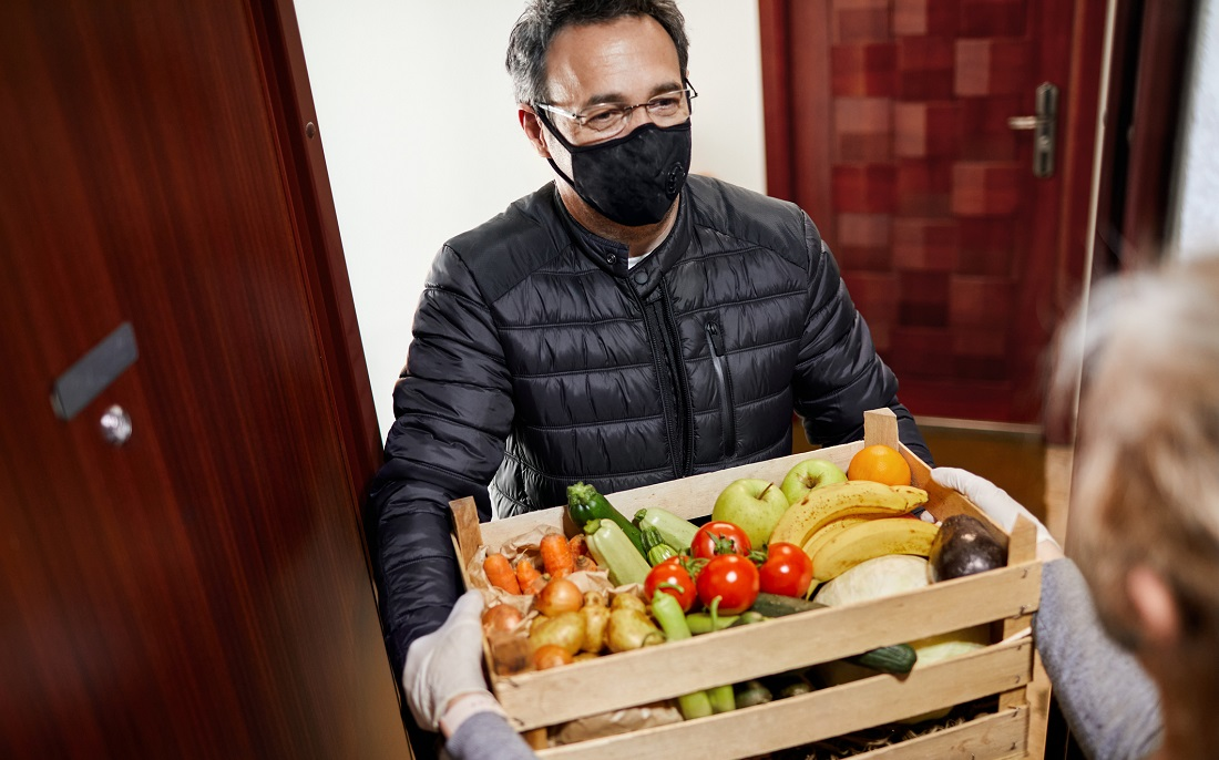 Man in black reusable face mask delivering crate of vegetables to elderly woman