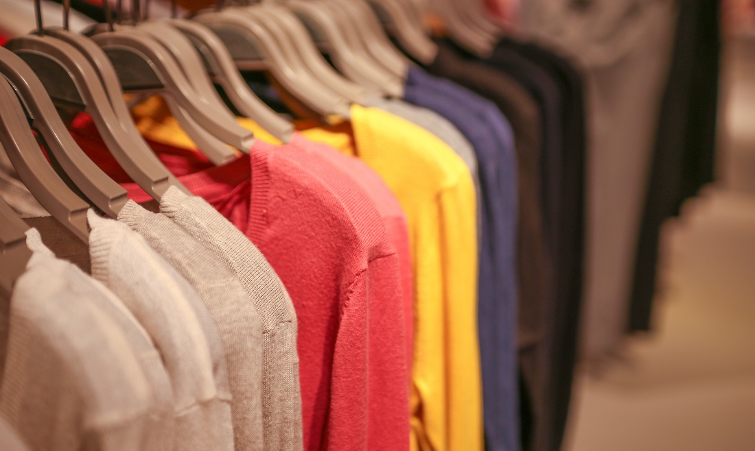 white, pink, and yellow sweaters hanging on a clothing rack