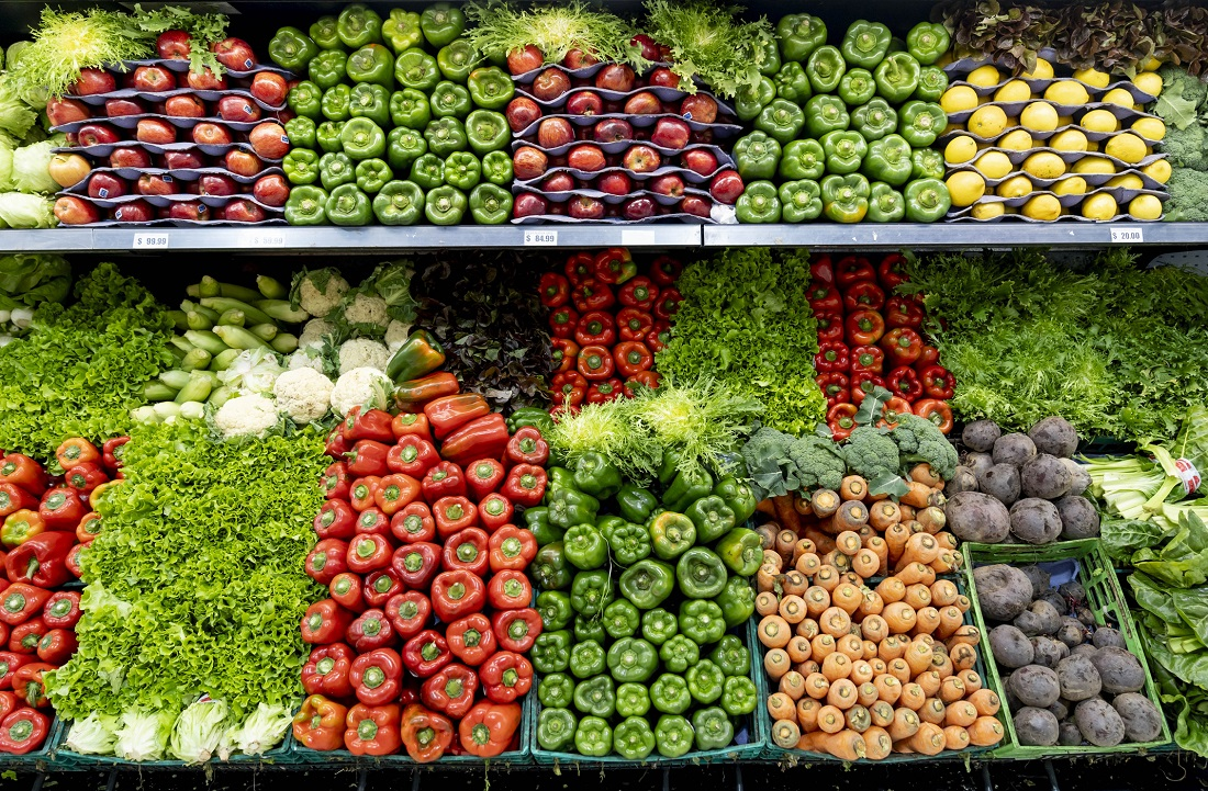A variety of fruits and vegetables neatly on display in the produce section of a grocery store