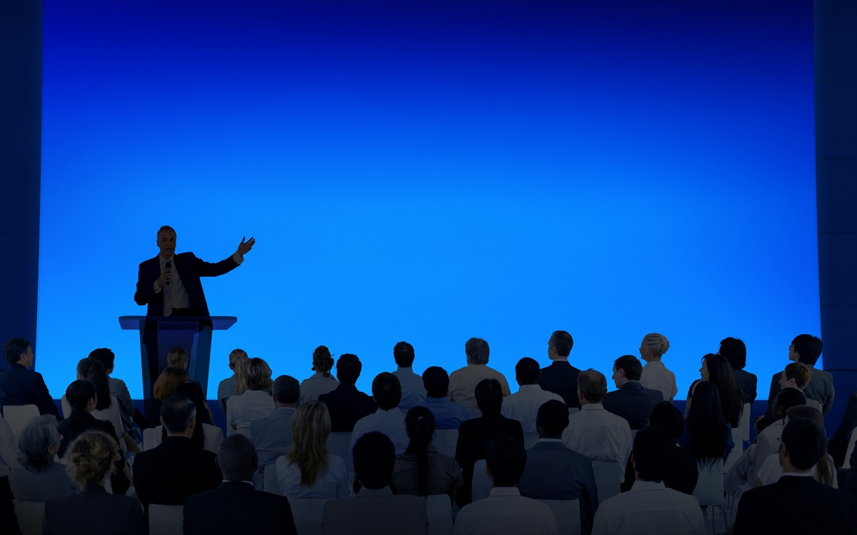 Man on stage behind a podium speaking to an audience and his backdrop is a large blue screen
