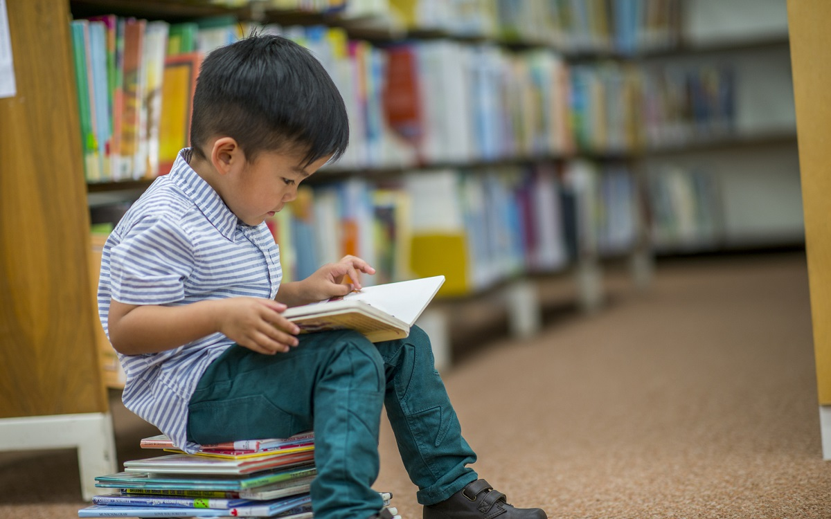 little boy sitting on a stack of books in the library and reading