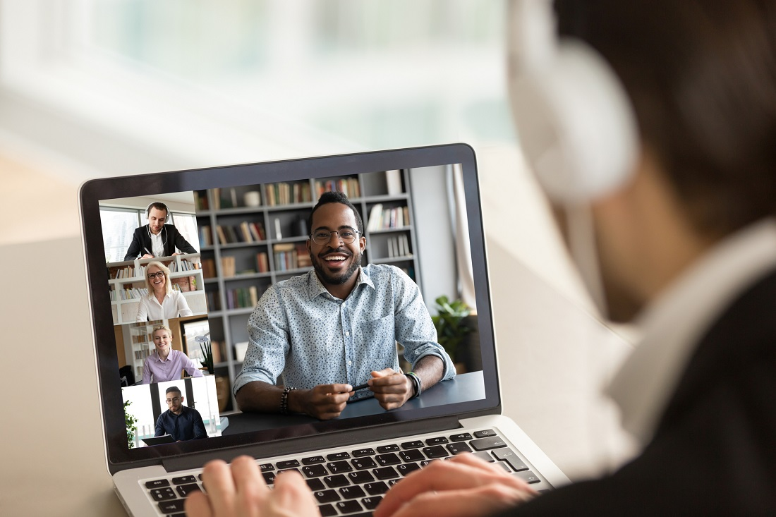 Back view of male employee talking on video call with diverse smiling colleagues