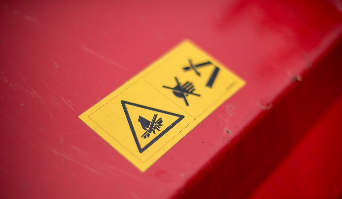 Yellow warning label on a red lawn mower