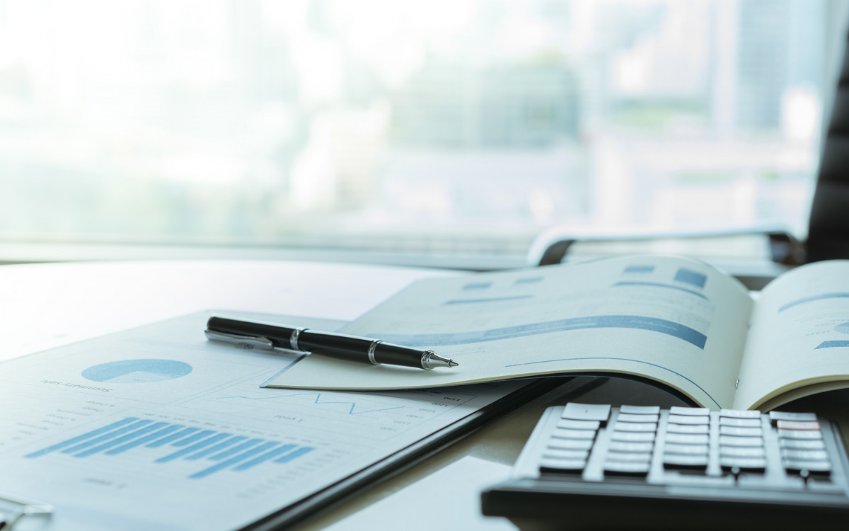 Pen with business report and calculator on financial advisor desk.