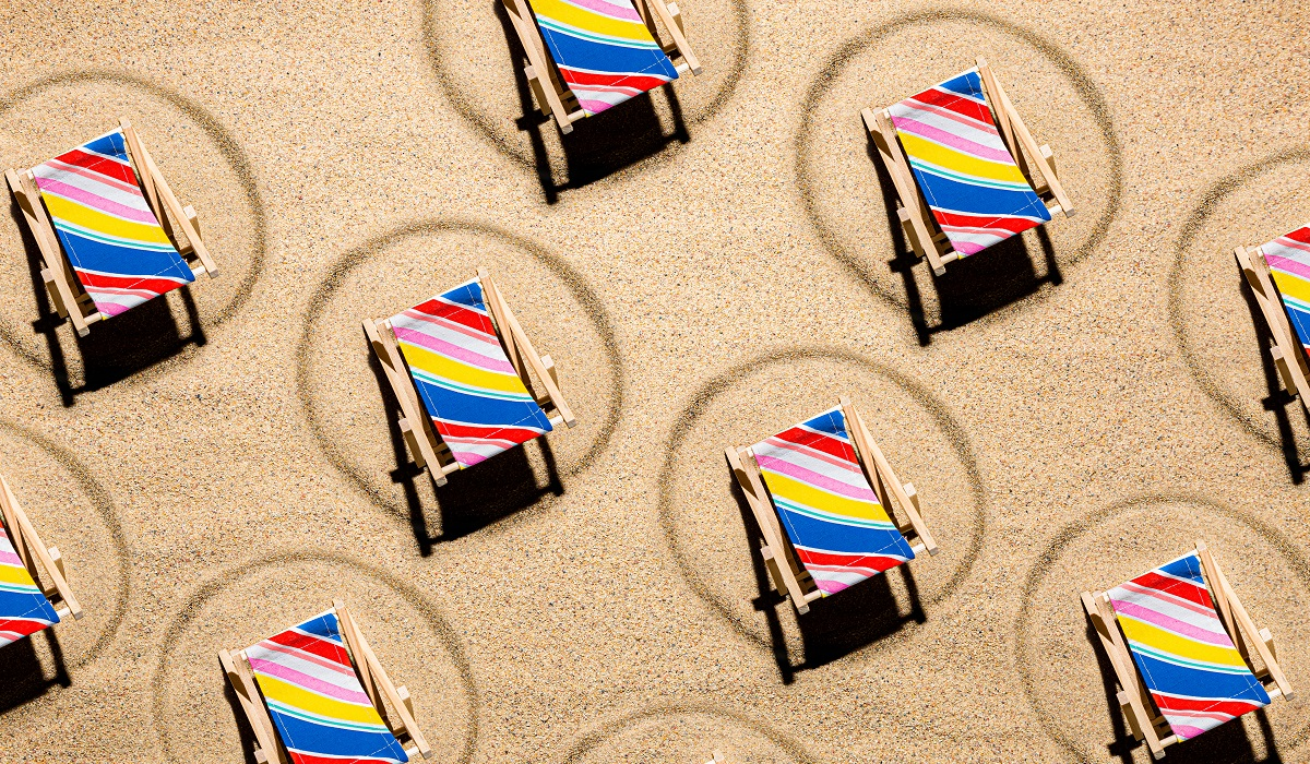 Colorful beach chairs on sand spaced apart for social distancing