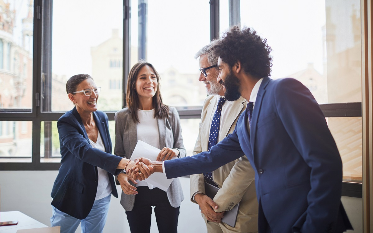Four business associates meeting in a conference room, smiling and shaking hands