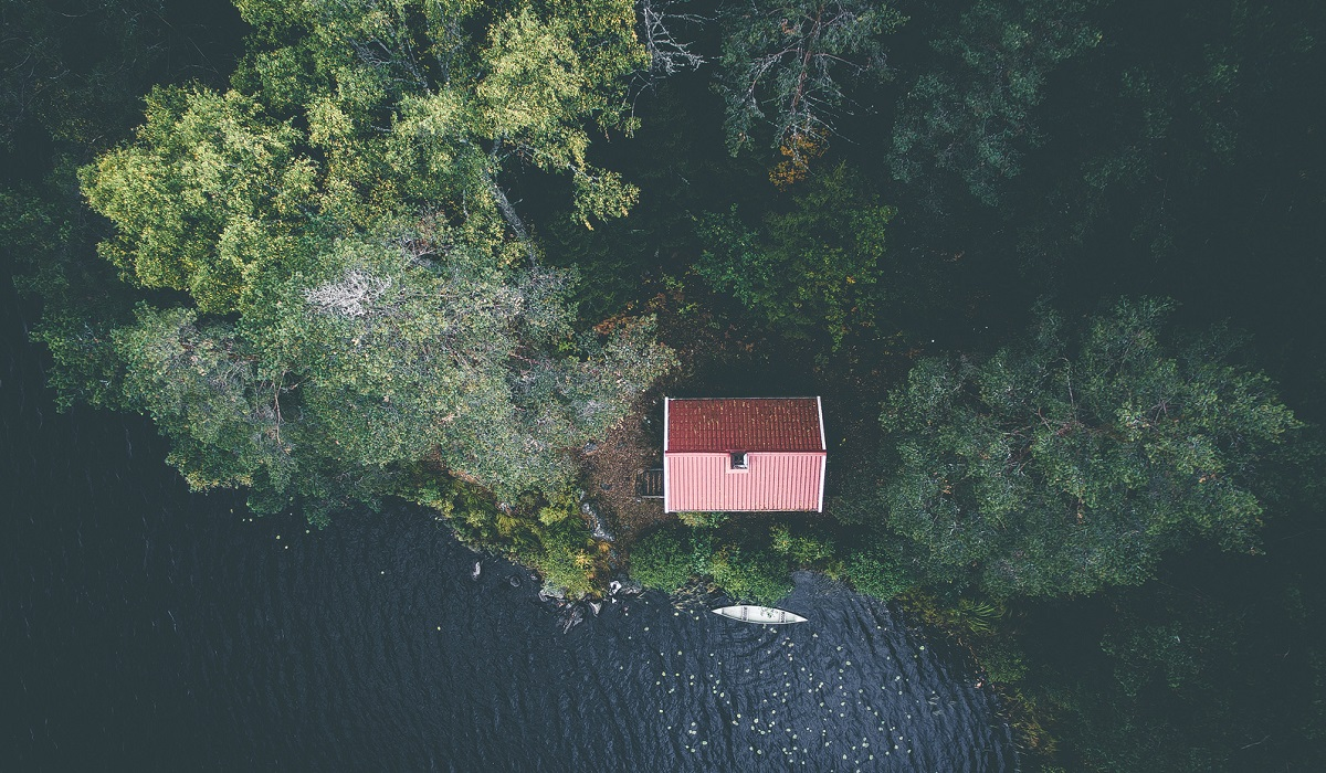 Aerial view of a cabin in the woods near the edge of a lake