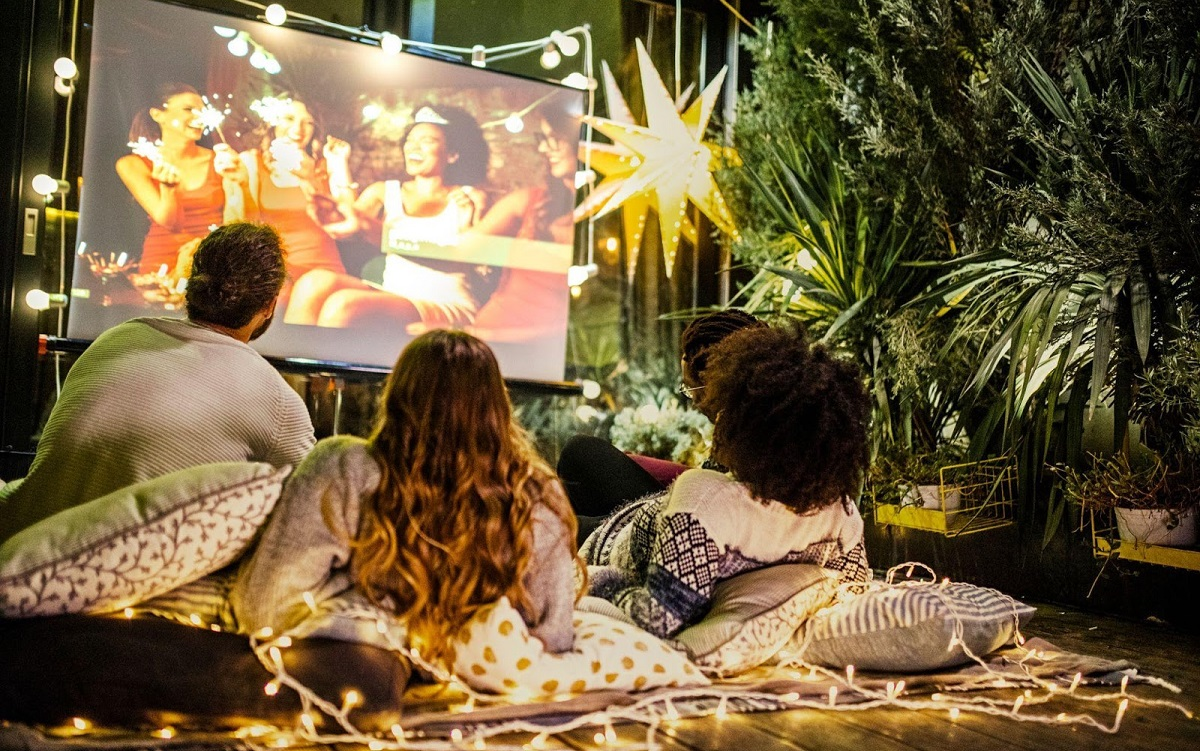 family watching movie on large screen outdoors