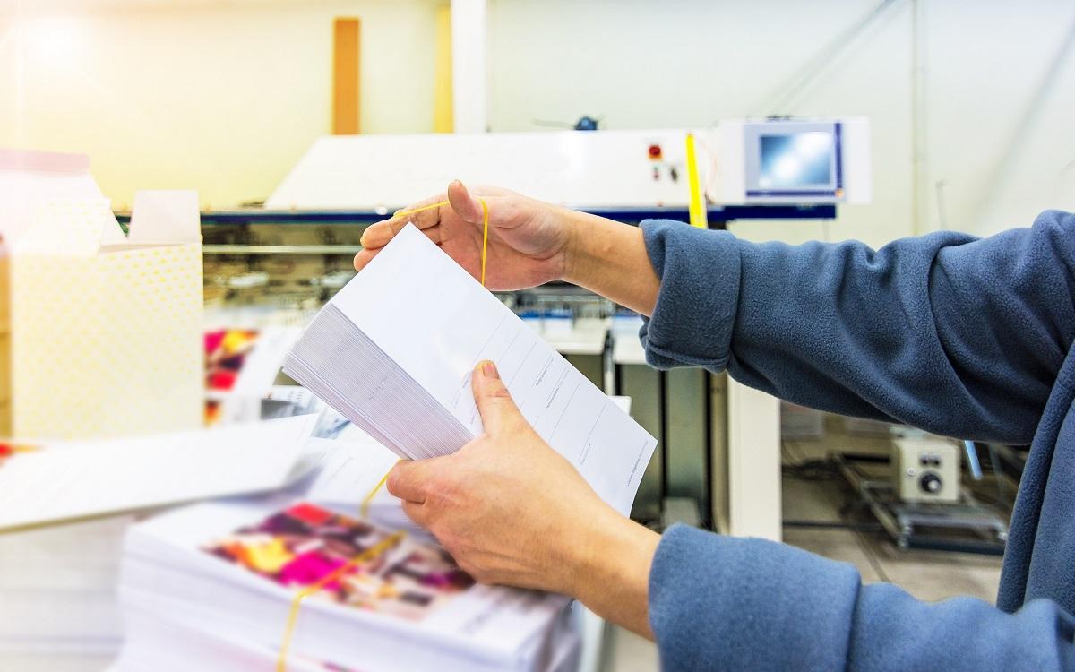 Workers hands manipulating envelopes for mailing