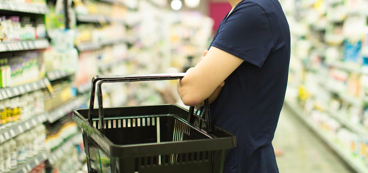 Shopper holding basket and looking at a store shelf stocked with vitamins
