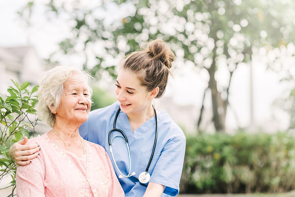 Young nurse in scrubs with her arm around an elderly patient