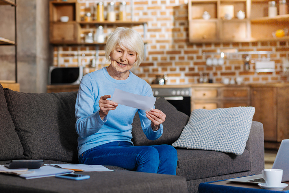 Woman with white hair seated on a couch reading mail