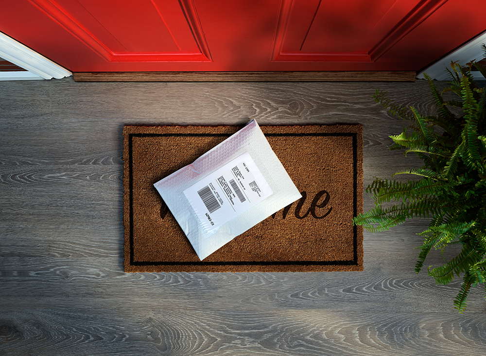 White padded envelope on a welcome mat on the porch of a house with a red door