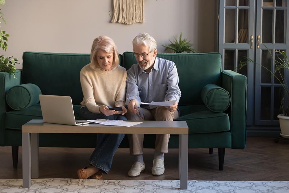 Smiling elderly spouses paying bills online using laptop