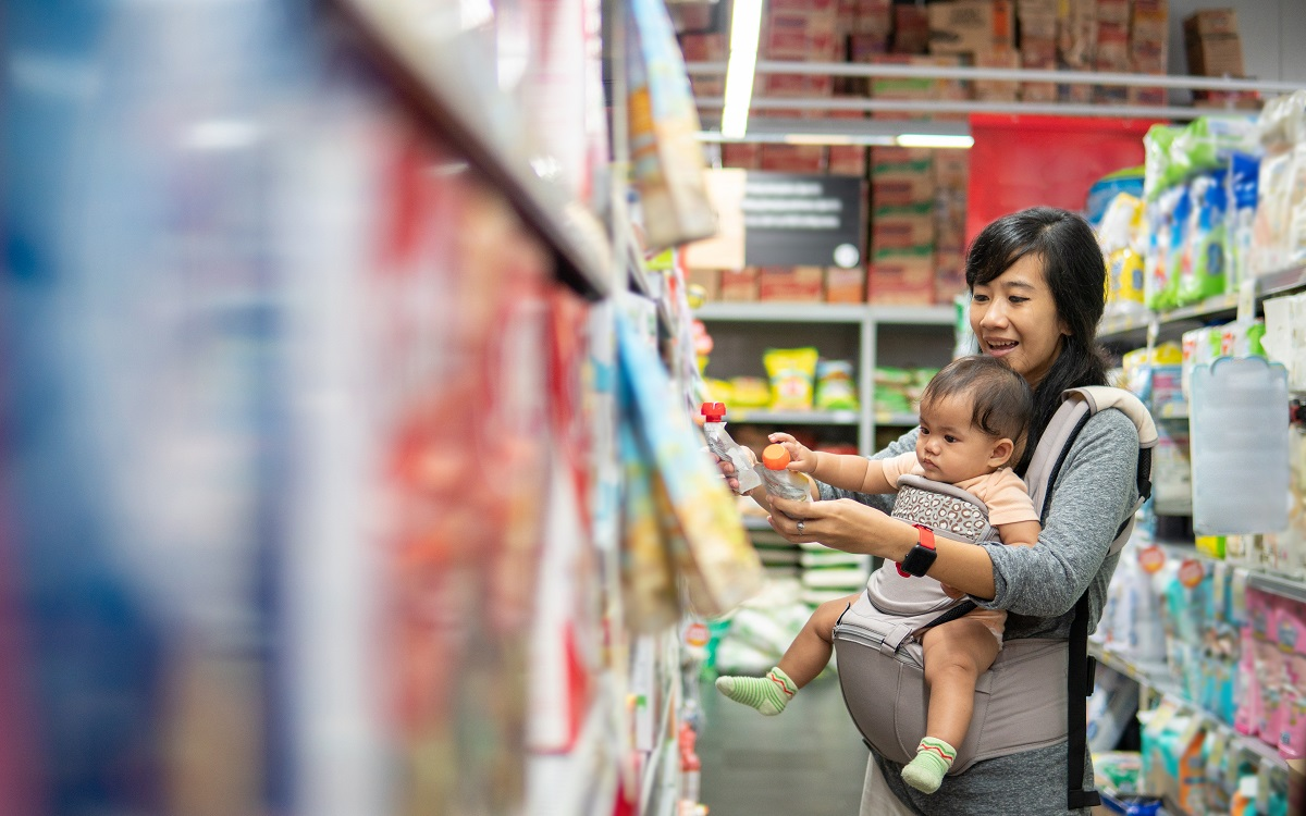 mother wearing baby in forward-facing baby carrier and shopping at supermarket