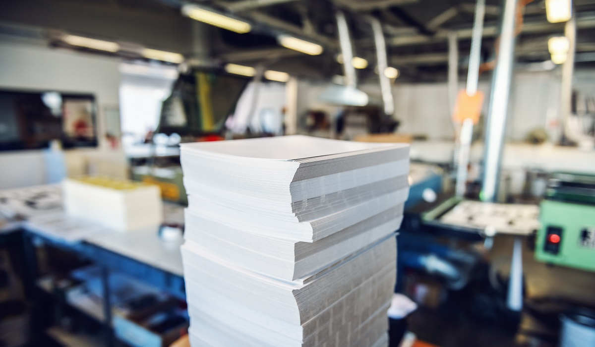 Picture of printing shop interior with a selective focus on pile of sheets.