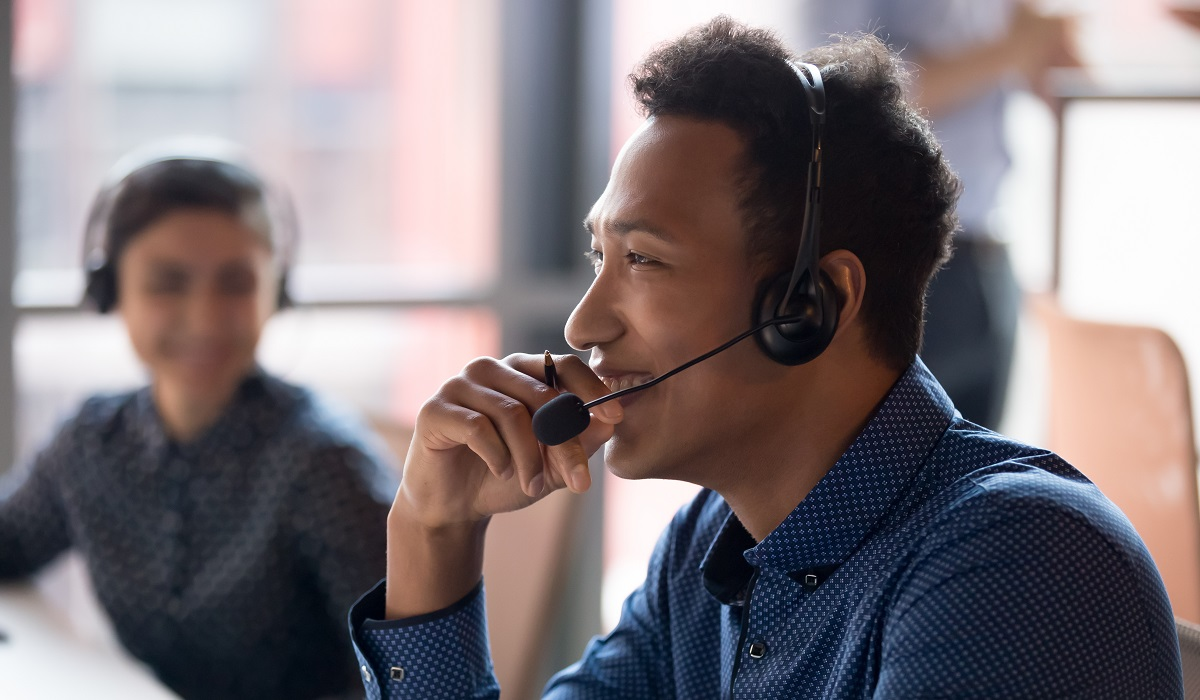 Smiling young call center agent laughing at workplace
