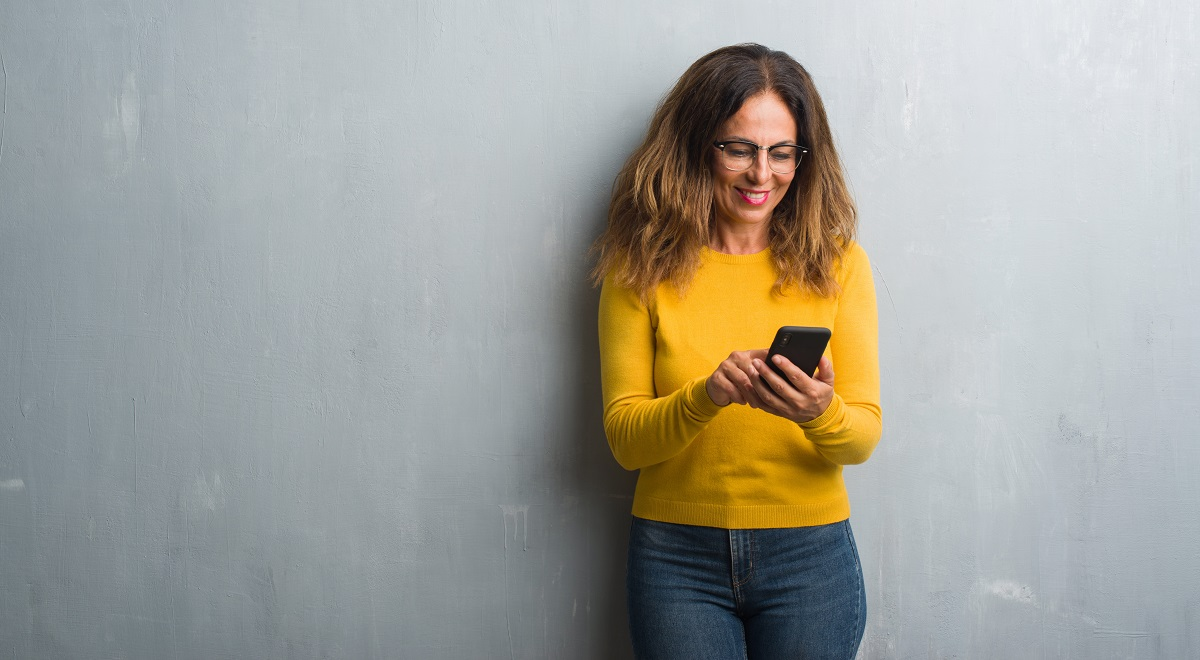 Middle age woman in yellow sweater using smartphone standing and smiling