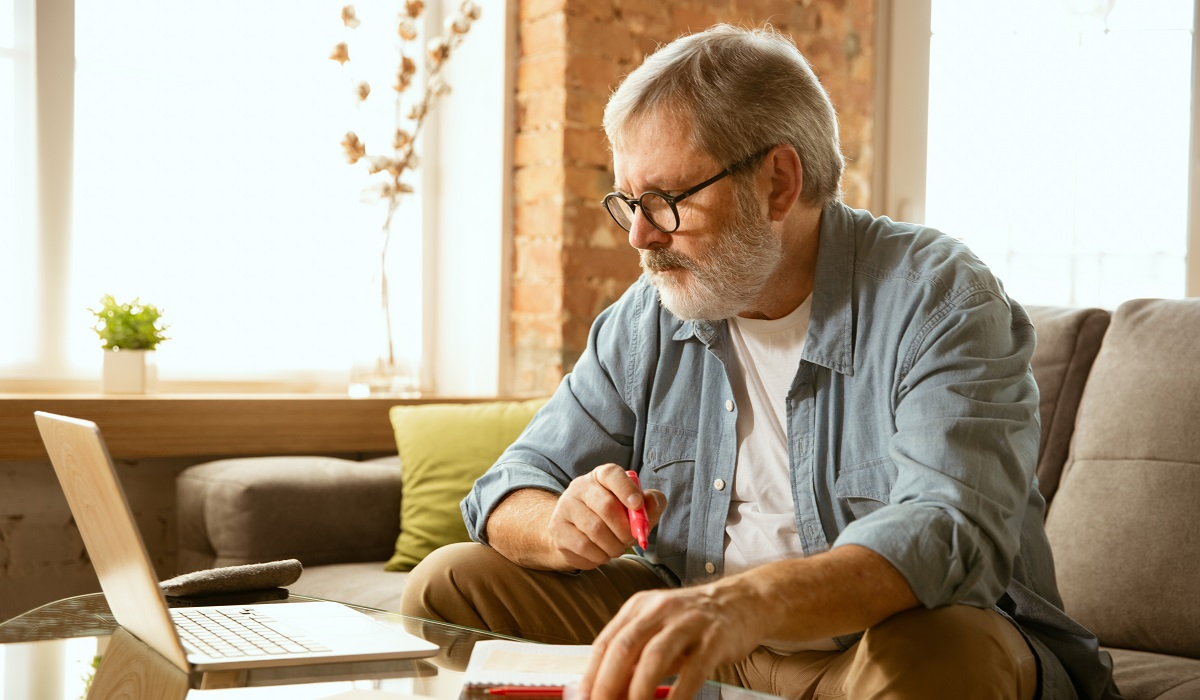 Senior man sitting on his sofa and working with laptop at home.