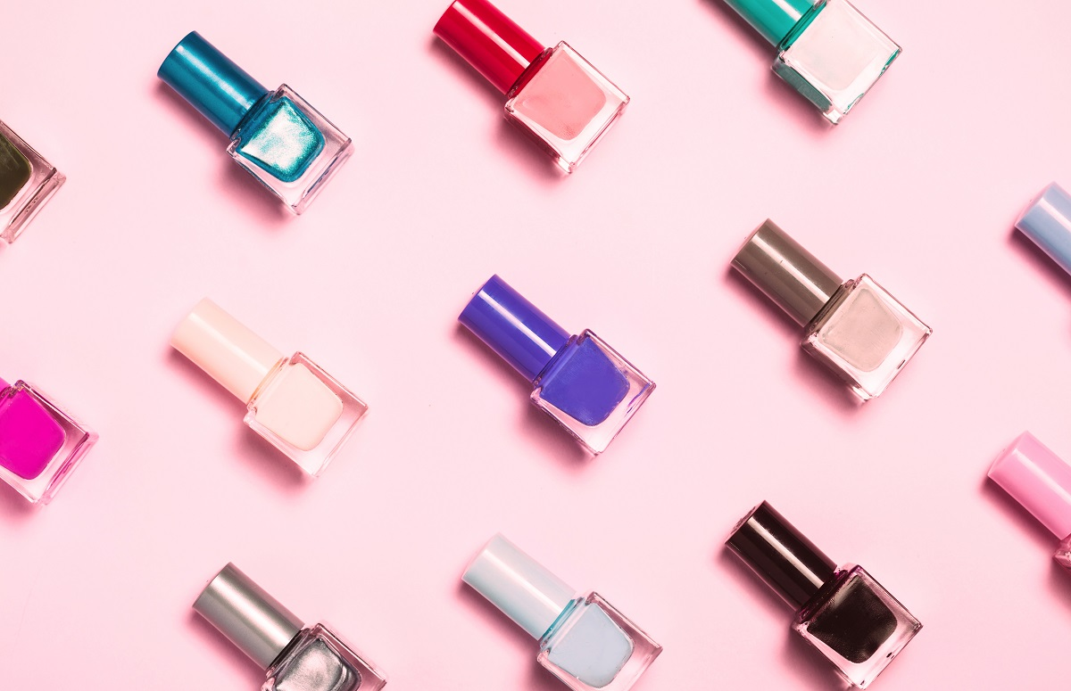 close up of nail polish bottles patterned on a pink background