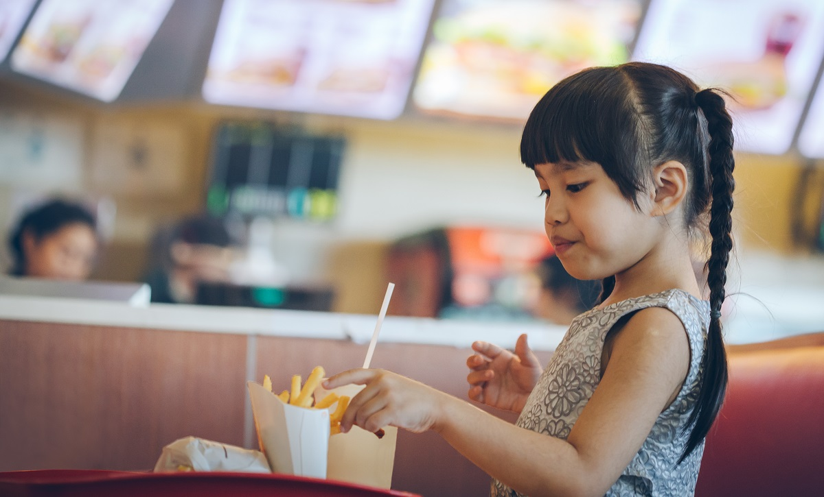 Young girl eating french fries at fast food restaurant