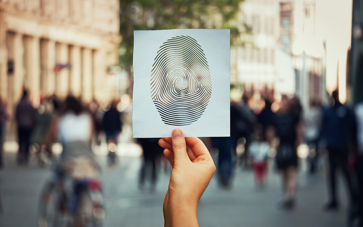 hand holding a printed picture of an enlarged fingerprint