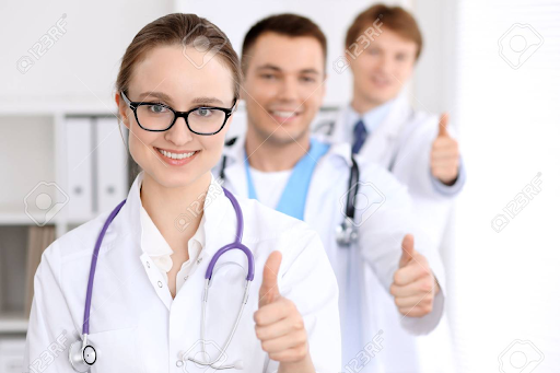 Three happy doctors giving thumbs up sign