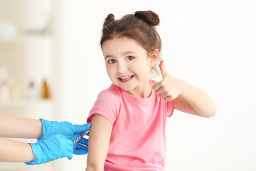 Young girl getting a shot and giving a thumbs up
