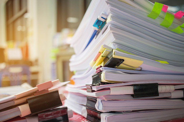 A photo shows a big sheaf of papers and reports toppling over on a desk, symbolizing the size and complexity of a content strategy