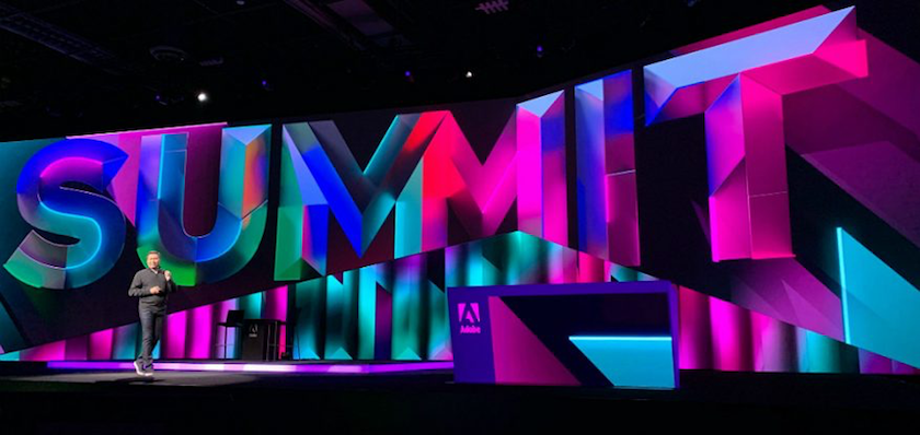 "A photo of the stage at the Adobe Summit 2019 showing a dramatic backdrop with the word ""Summit"" in 10-foot letters."