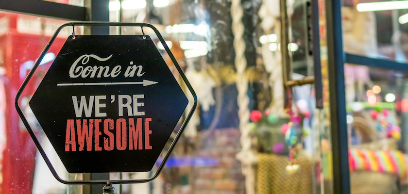"A photo of a sign in a shop window. The sign boldly reads: ""Come in, we're awesome!"""