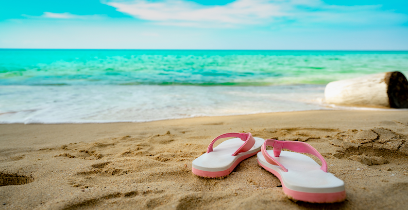 A pair of pink sandals lie on the sand next to the ocean and a bright blue sky.