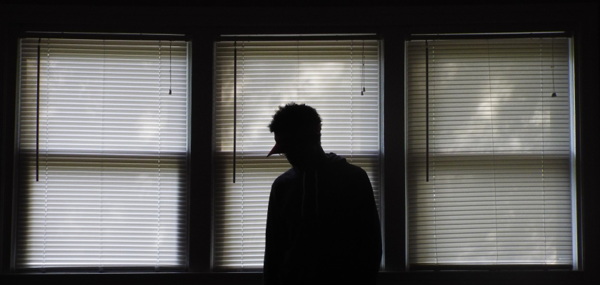 A dark figure lurks against a set of drawn blinds filtering in the light, representing the hidden threat that MKT-TOK data can pose to marketers and their companies.
