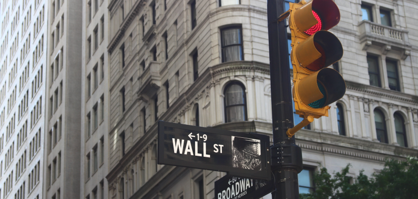 Photo shows street signs for the intersection of Wall Street and Broadway, a major financial district.
