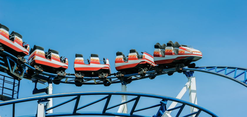 Red and white striped roller coaster cars fly around a bend in the tracks against a blue sky.