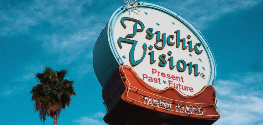 """A neon sign advertises """"psychic visions"""" and tarot card readings, symbolizing the predictions that marketers need to make about marketing budgets."""