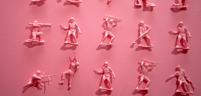 A photo shows an art project that comprises a pink wall covered with pink toy plastic soldiers.