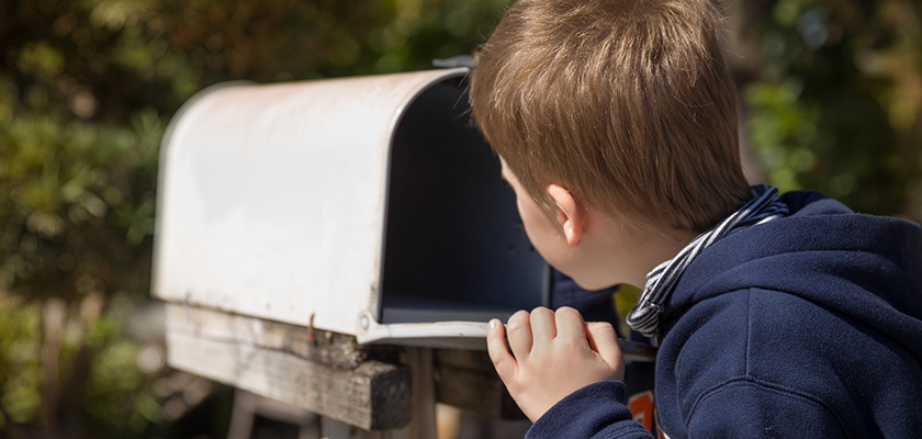 Young boy peeking into an open inbox to find mail deliveries
