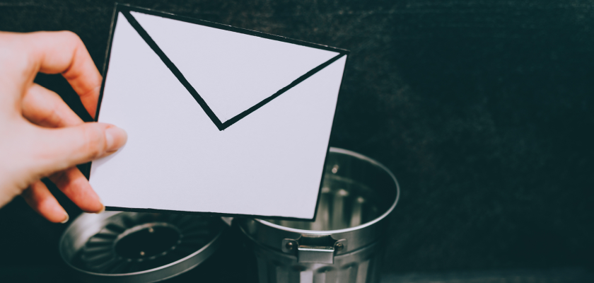 Hand holding email impacted by anti-spam tools over a tiny trashcan