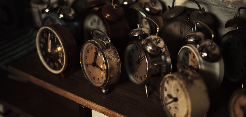 Wooden desk filled with rows of antique clocks to track timesavings for marketers
