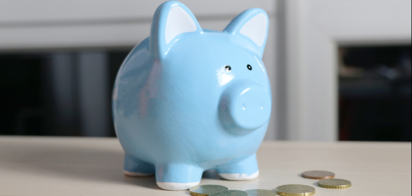 Light blue piggy bank surrounded by coins to support marketing budgeting efforts