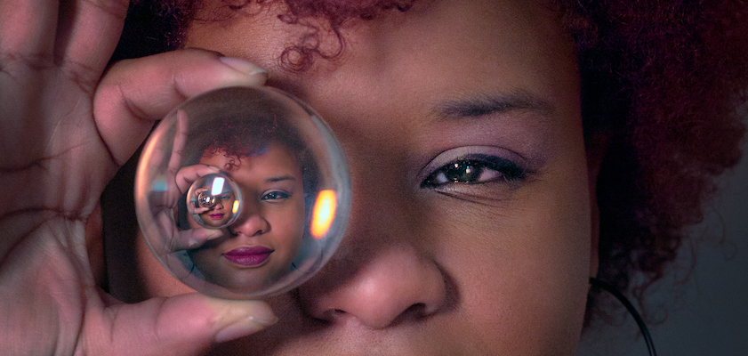 A woman holds a crystal ball up to her eye, representing the importance of seeing into the future through marketing forecasting.