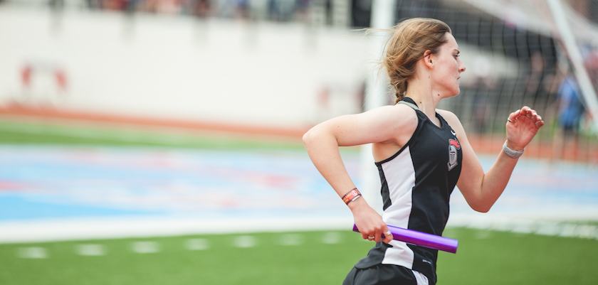 A female runner races with a baton in her hand, ready to pass it to the next runner.
