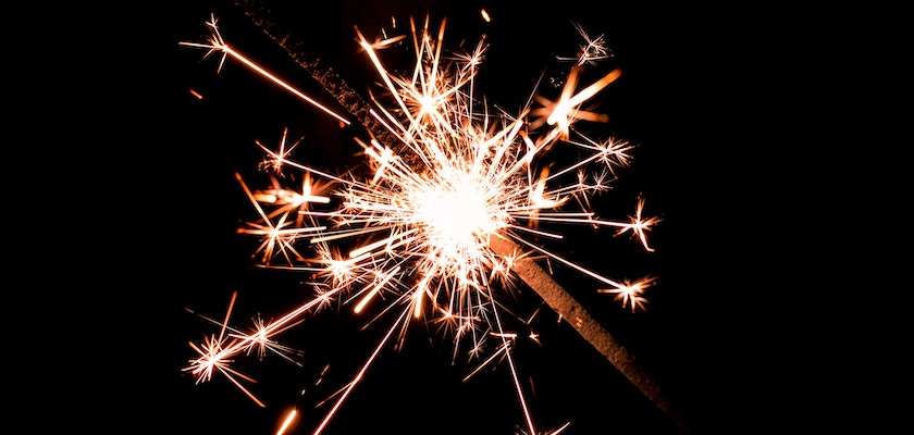 A blazing sparkler against a striking dark background represents the celebration of DemandLab's SLMA awards.