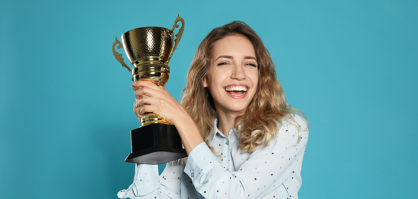 young woman holding golden trophy against blue background representing DemandLab CEO SLMA award win
