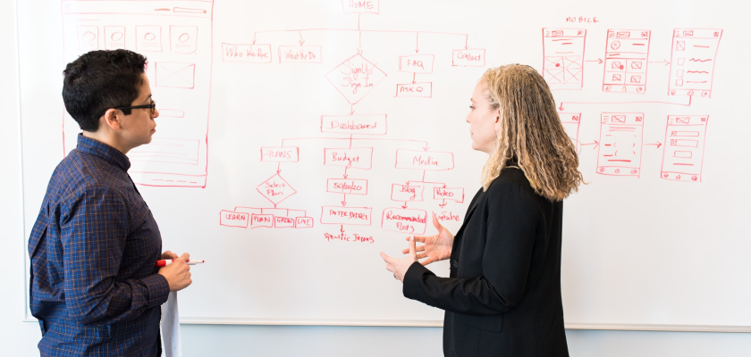 Two digital marketers stand in front of a whiteboard with flow diagrams.