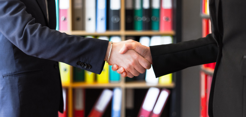 A close-up of a handshake between two businesspeople represents the new partnership between DemandLab and Marketo.