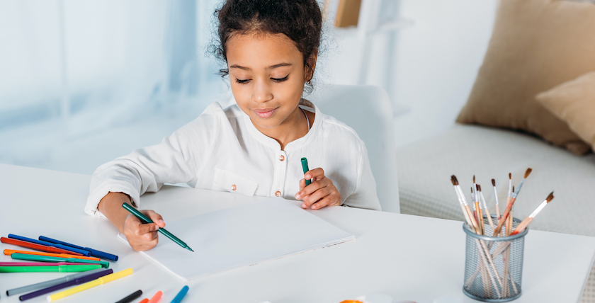Adorable african american kid drawing with felt pens at home
