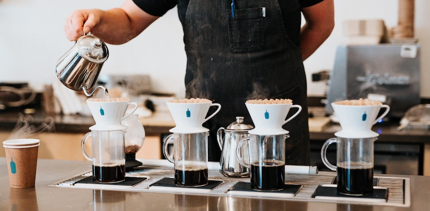 Coffee shop worker pouring hot coffee through filters similar to Marketo smart filters set up